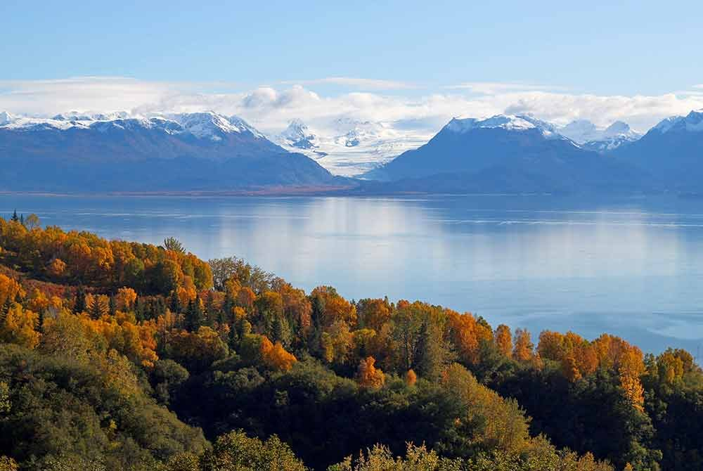 snow-capped mountains across a lake with autumn trees