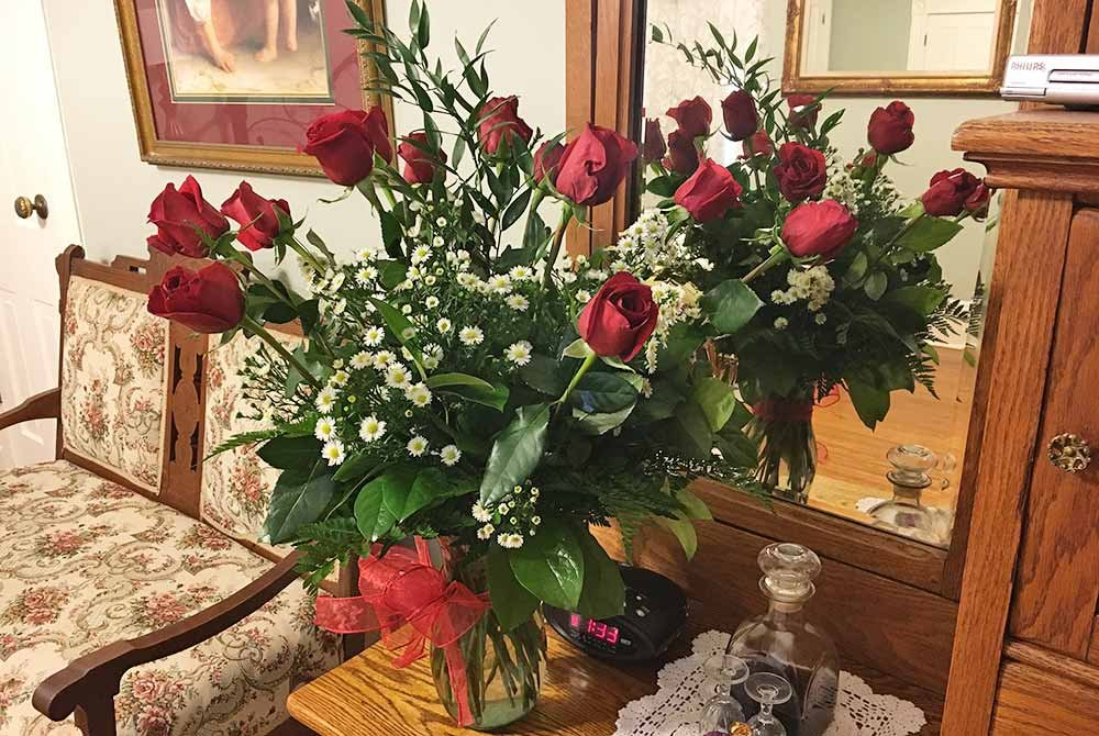Roses in vase by mirror