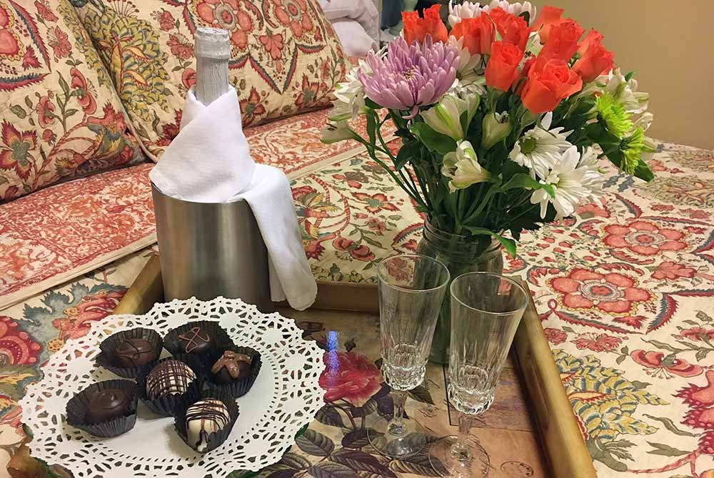 Chocolates and champagne on serving tray with flowers