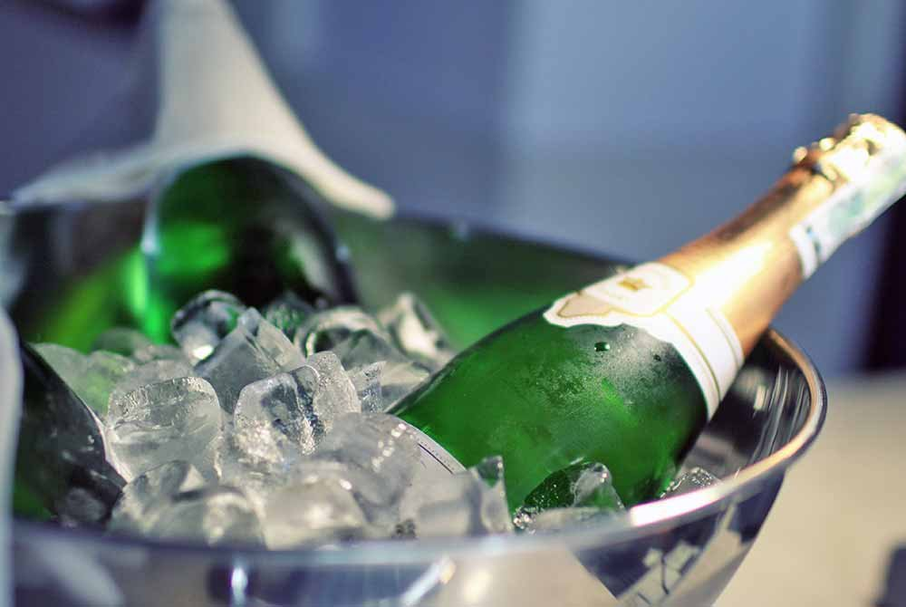 Champagne bottle laid in bowl of ice