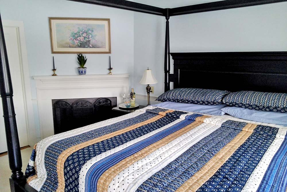 Quilted four-post bed next to fireplace