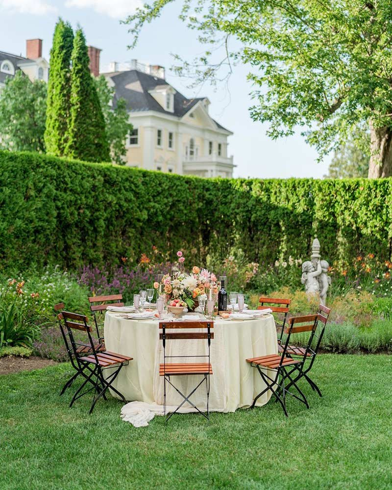 Decorated dinner table in yard surrounded by hedges