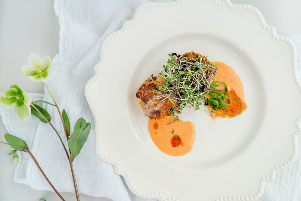 crab cakes with herbs plated with green flowers