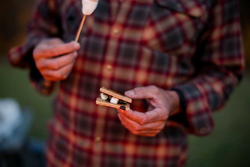 man in plaid flannel holding smores