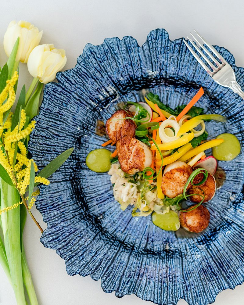 scallops and fresh vegetables plated next to flowers