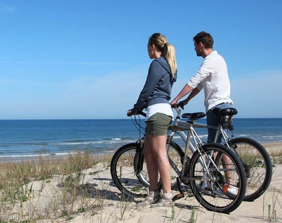 Man and woman with bikes on beach overlooking ocean