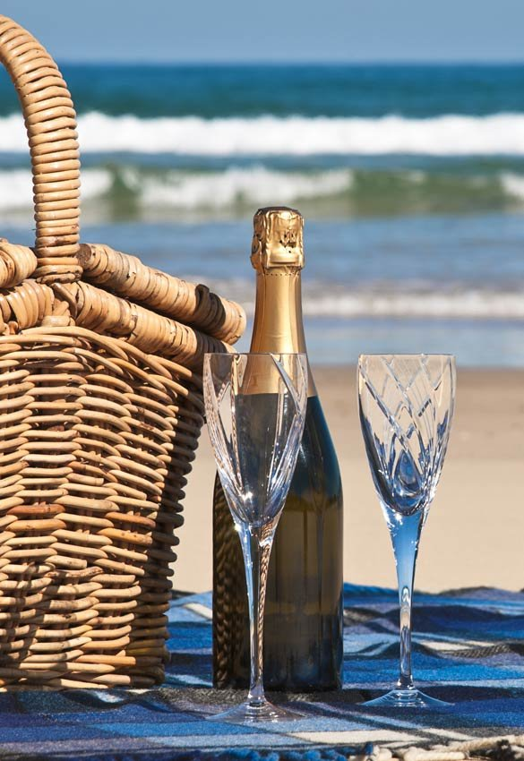 wine bottle and glasses next to basket on beach