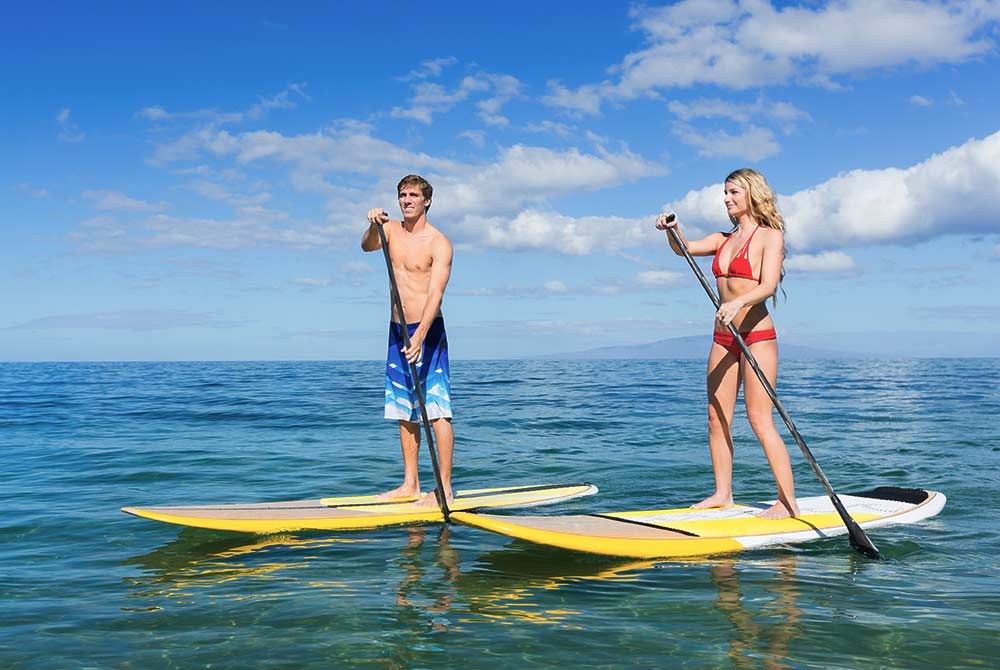 two people paddleboarding in the ocean