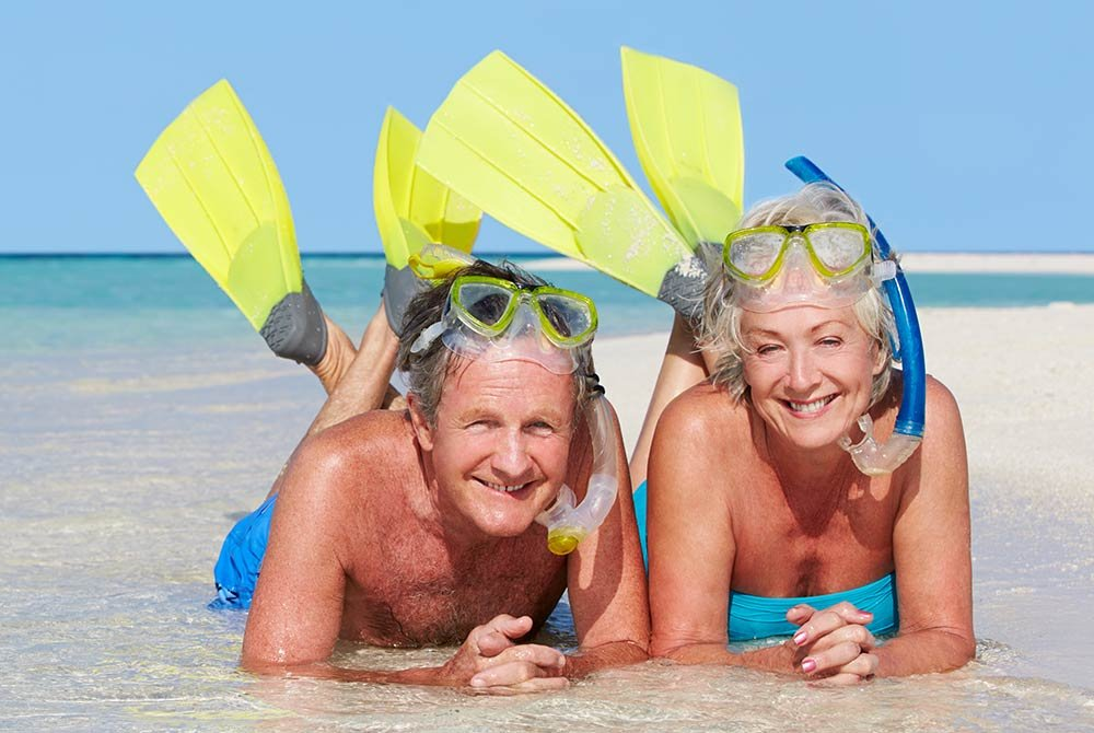 man and woman lying on beach with snorkeling gear