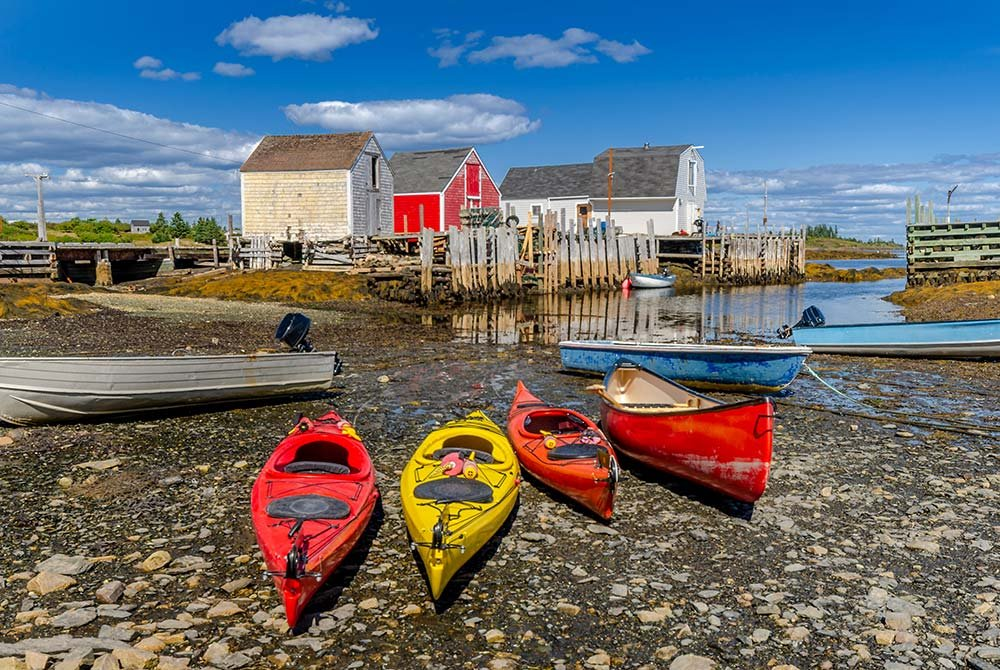 Kayaks laid on beach next to old barns