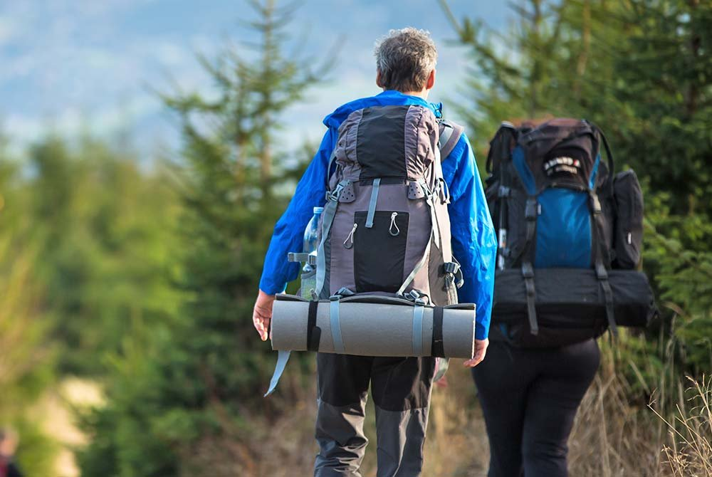People backpacking on hiking trail by trees