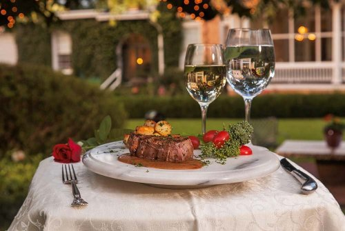 Steak and wine glasses decorated on outdoor table