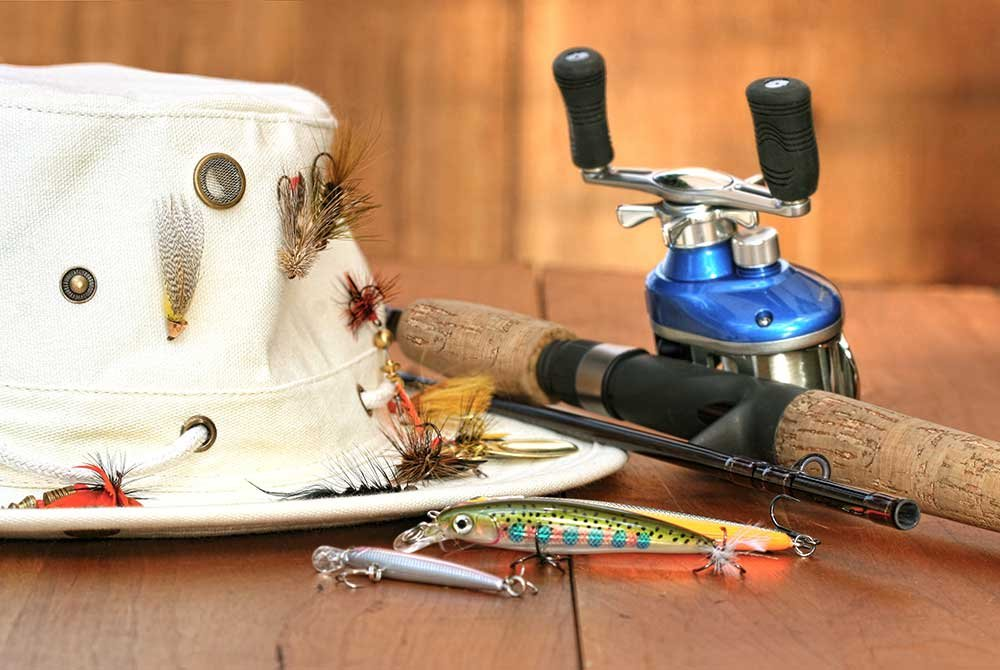 Fishing hat and fishing pole on table