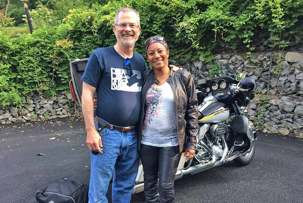 Couple standing in front of a motorcycle