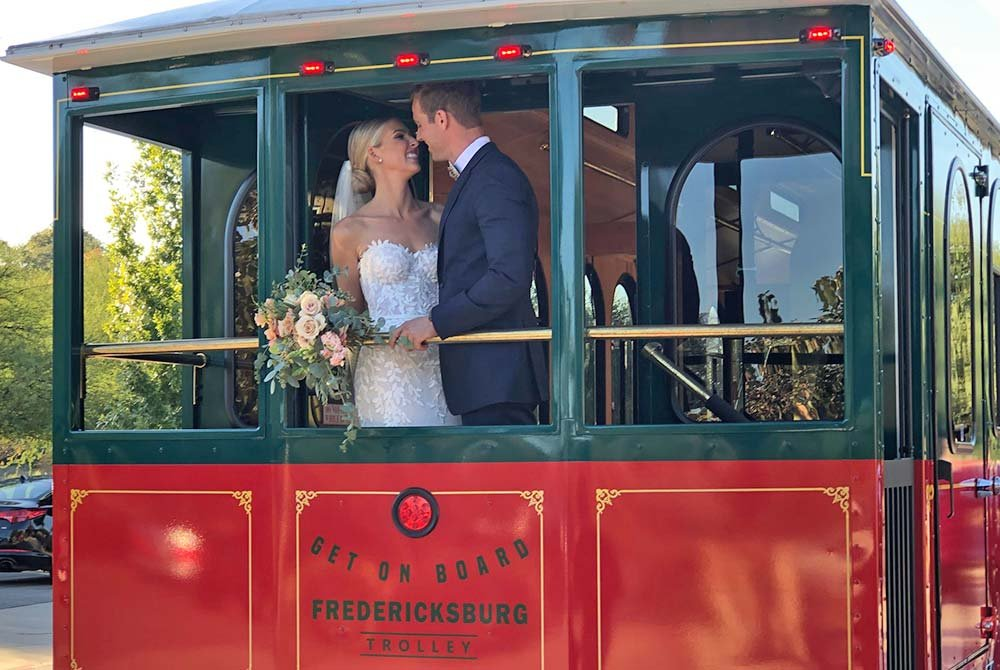 Bride and groom smiling on back of trolley