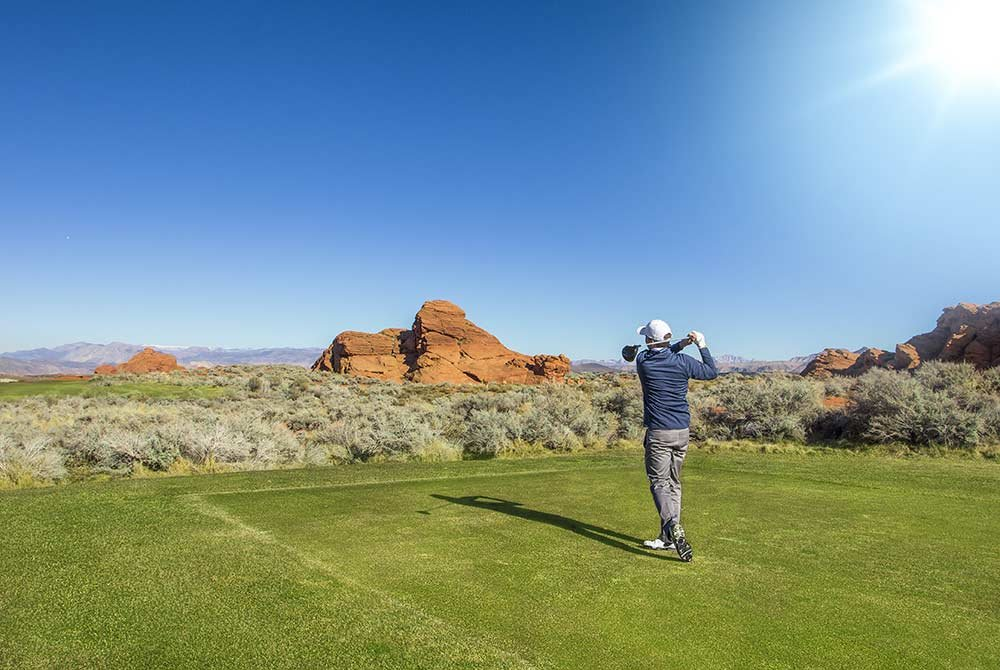 Man playing golf on a course near red rocks