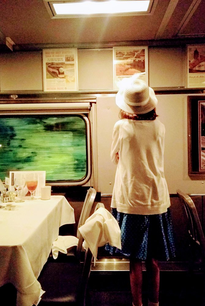 Girl standing next to dining table in a moving train
