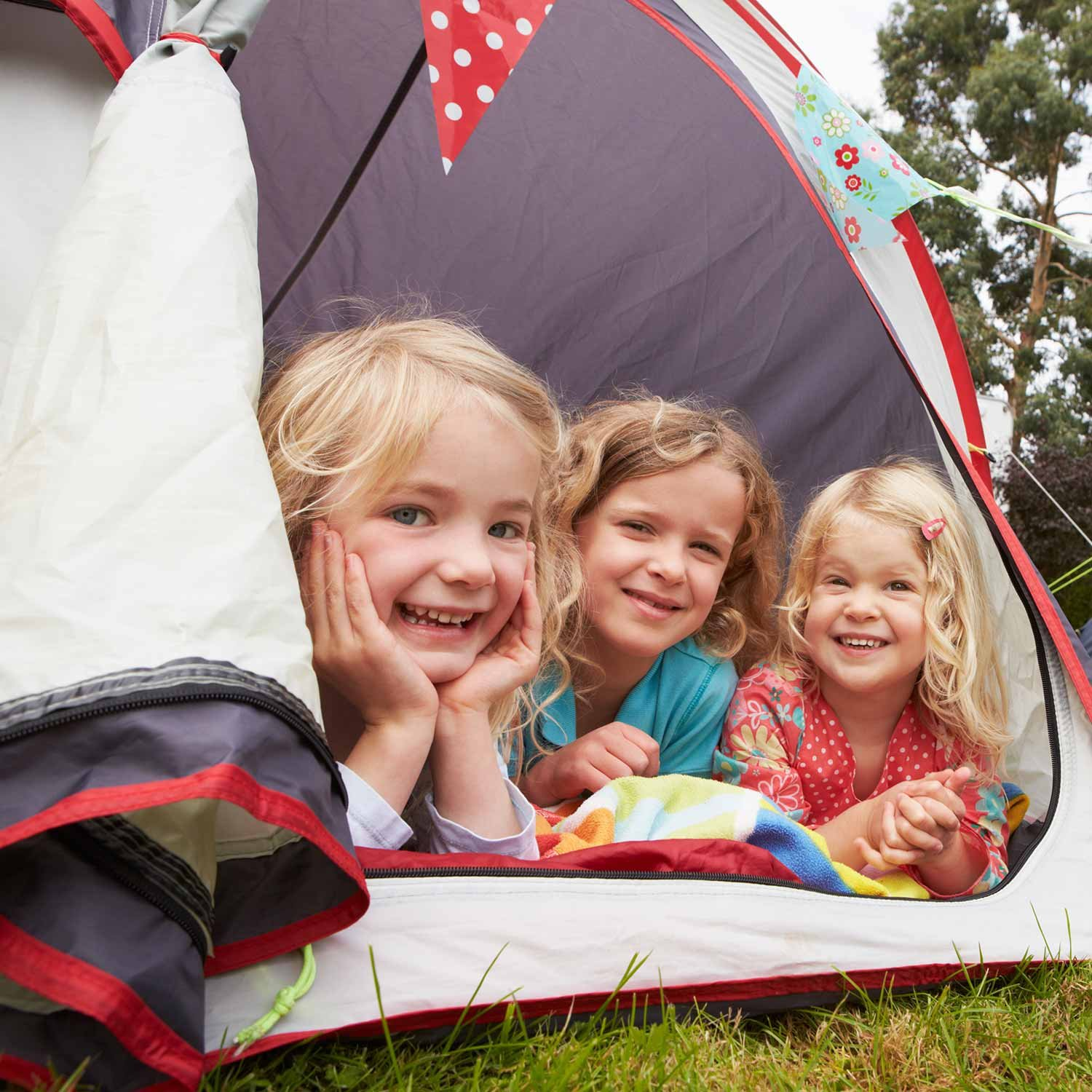 young girls smiling camping in a tent