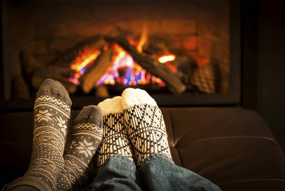 two people warming their feet by the fire