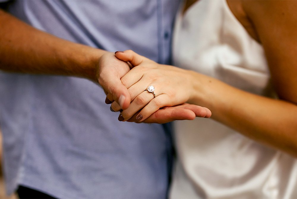couple holding hands and showing engagement ring