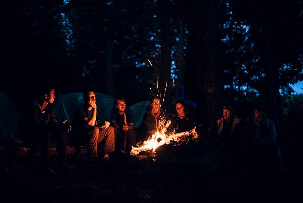 group sitting around campfire