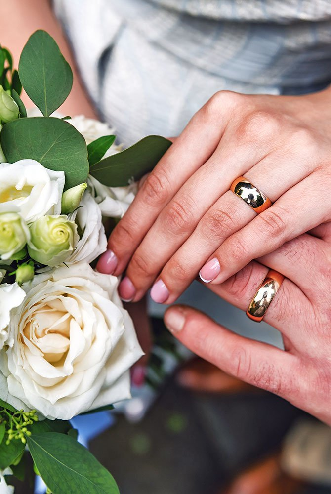 man and woman displaying rings next to bouquet of flowers