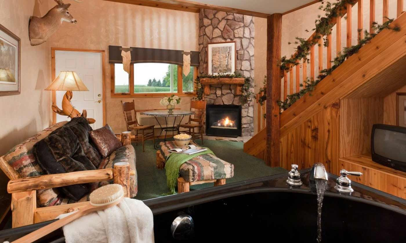 Lodge-styled room with jetted tub, fireplace, and couch