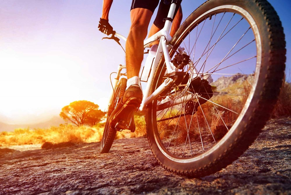 man riding a mountain bike into the sunset