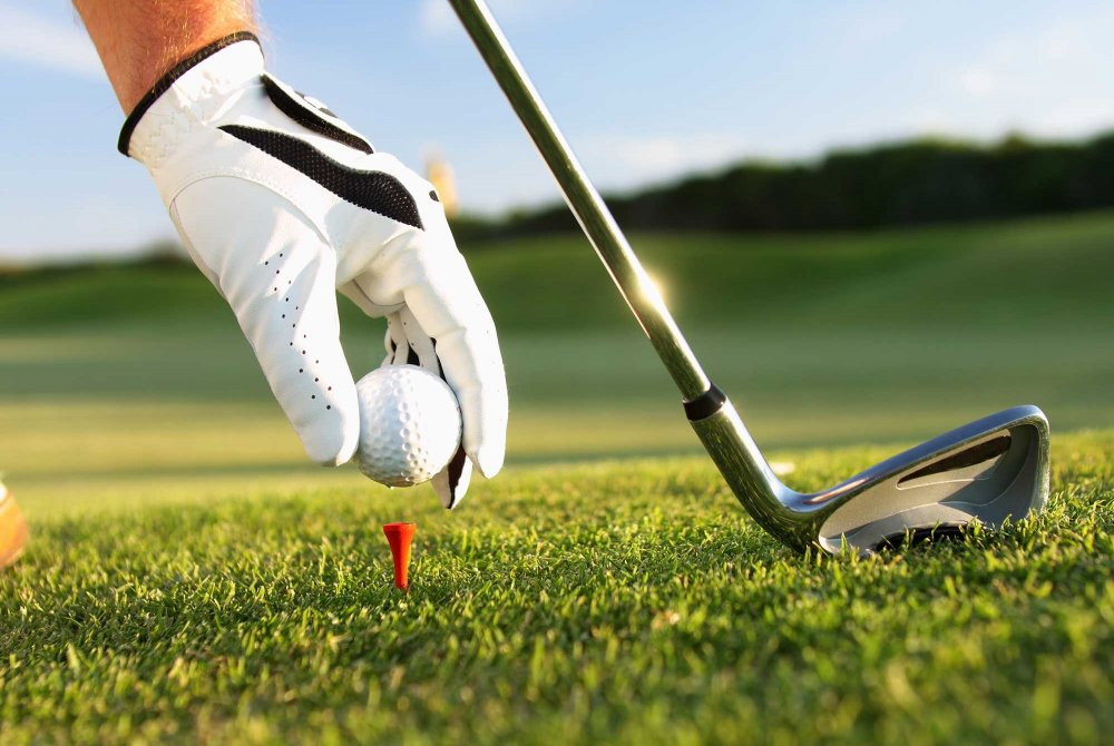 Close up of a man with golf glove placing a golf ball on the grass to hit pictured with golf club