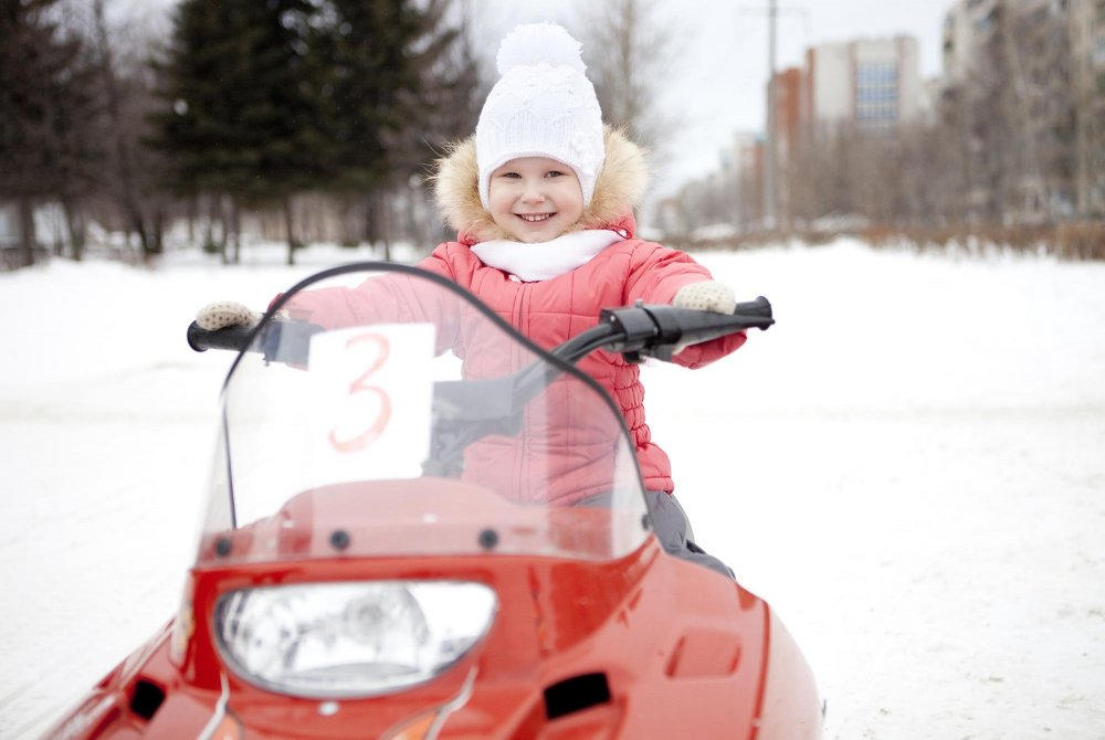 Young girl riding a snowmobile