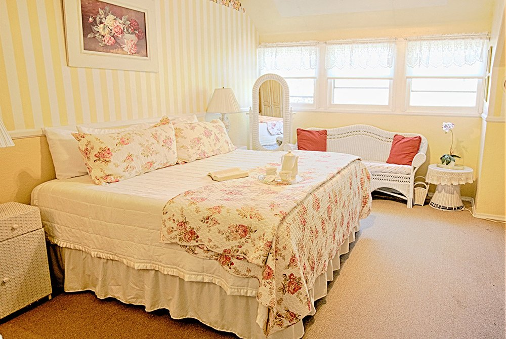 King bed in large room with seats and windows