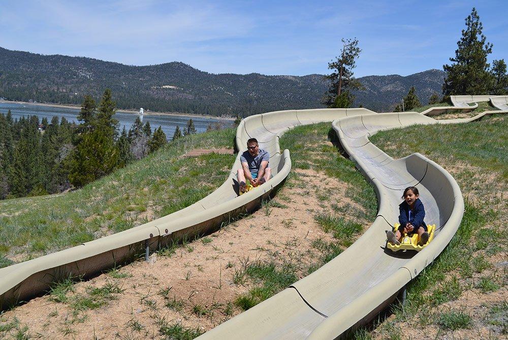 Children sledding down hillside slide
