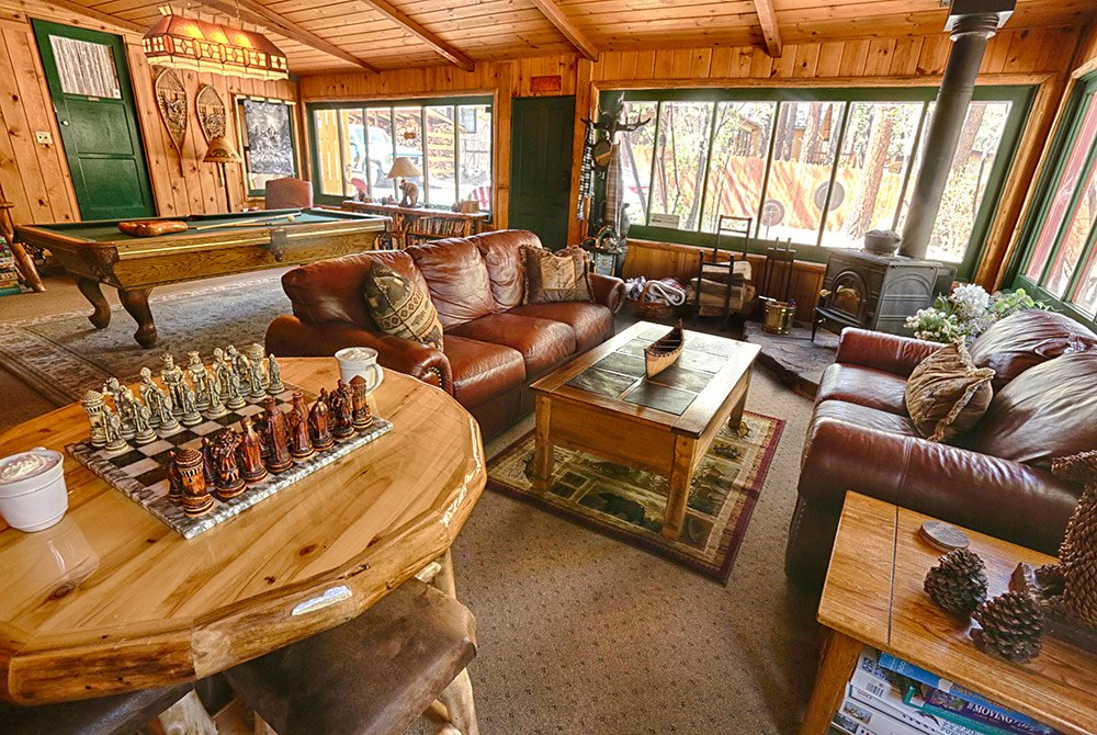 Living room with leather couches, pool table, chess board, and windows