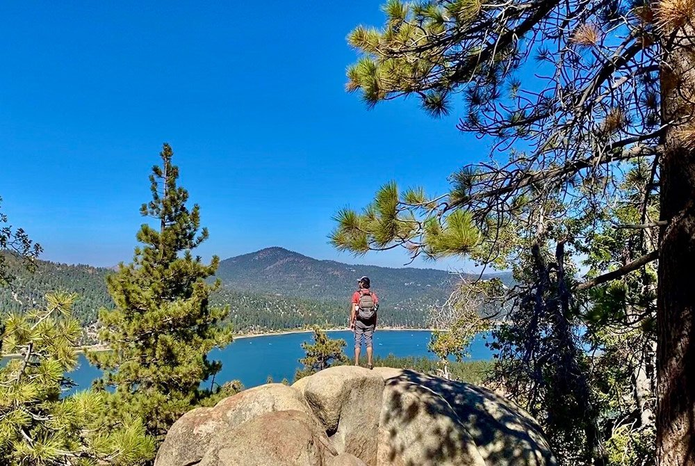 Hiker standing on large rock infront of lake