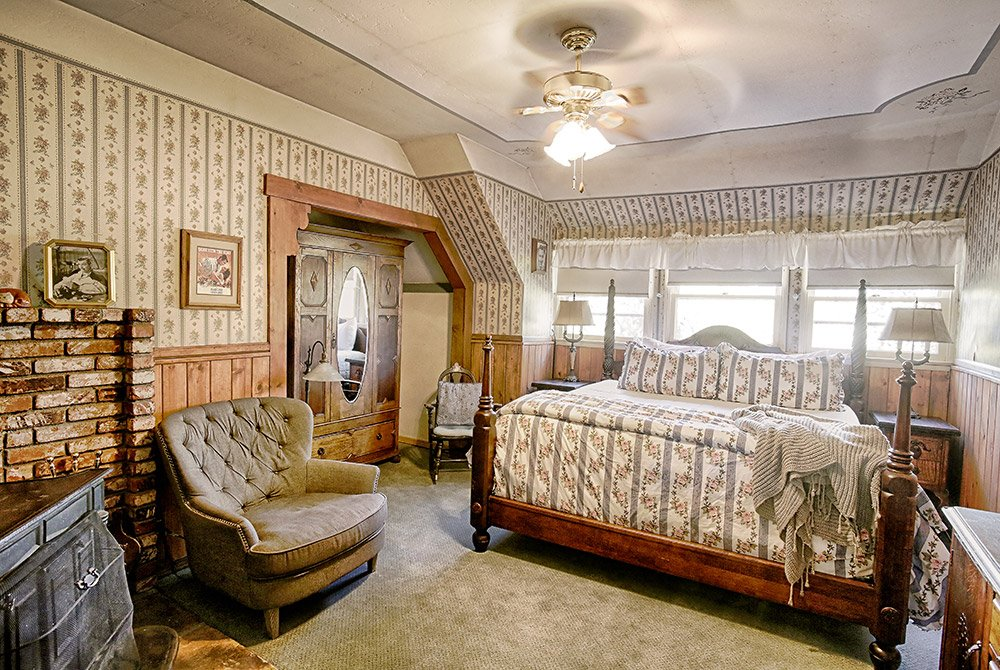 Large room with wardrobe, fireplace, seats, windows, and king bed