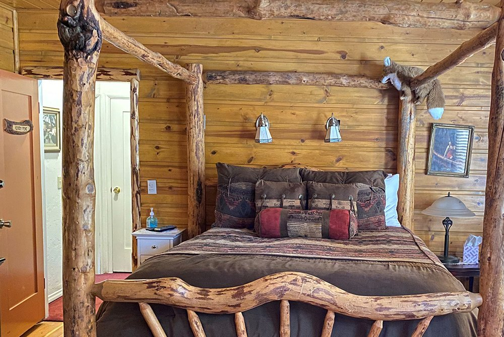 Large bed in a tall log frame