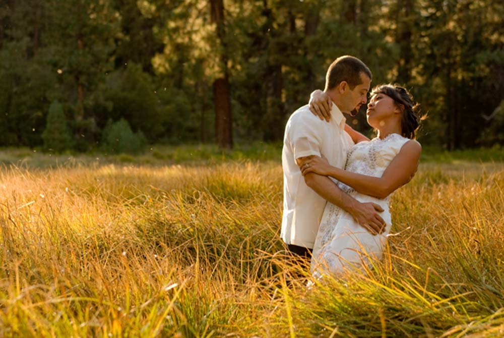 Bride and groom staring at each other in a field of grass