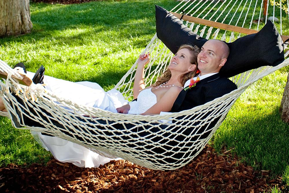 Bride and groom laying in an outdoor hammock