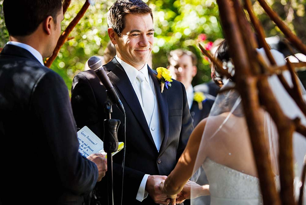 Groom smiling at bride next to officiant during ceremony