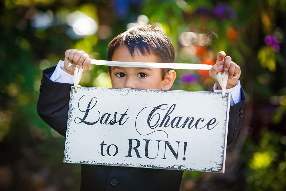 Young boy holding up last chance to run away sign