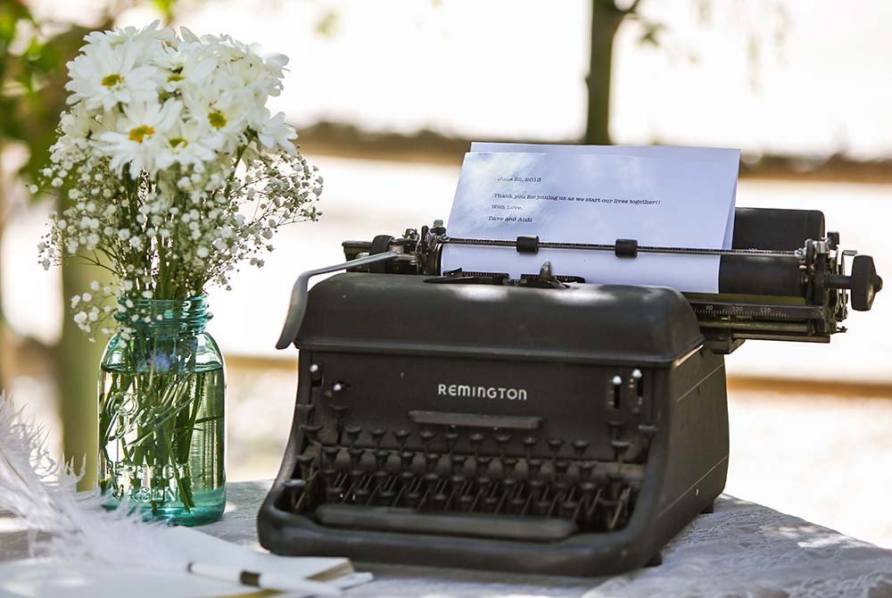 Typewriter and vase of flowers on table with tablecloth