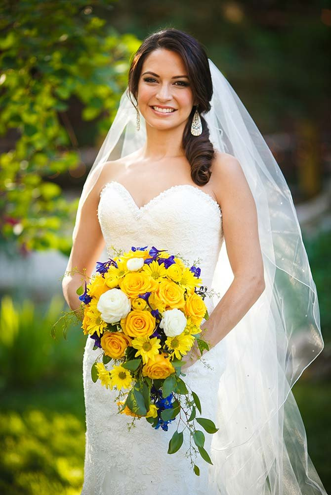 Bride smiling and holding bouquet of flowers