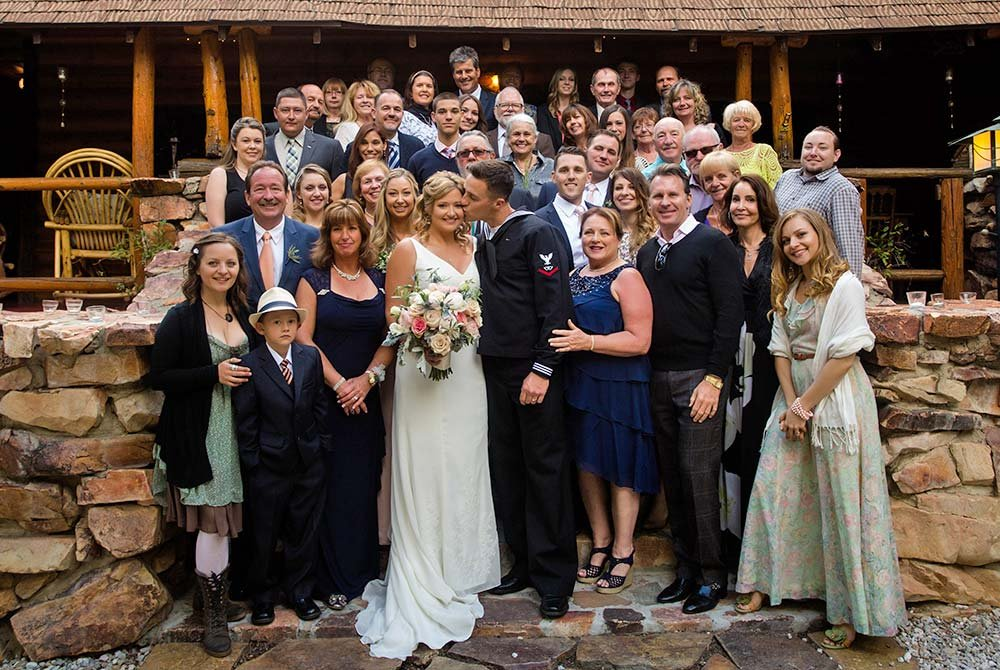Large gathering of people posed around bride and groom