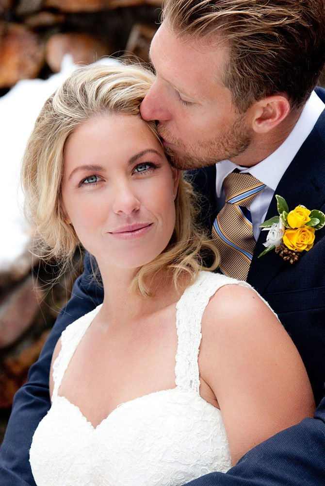 Groom kissing bride for picture