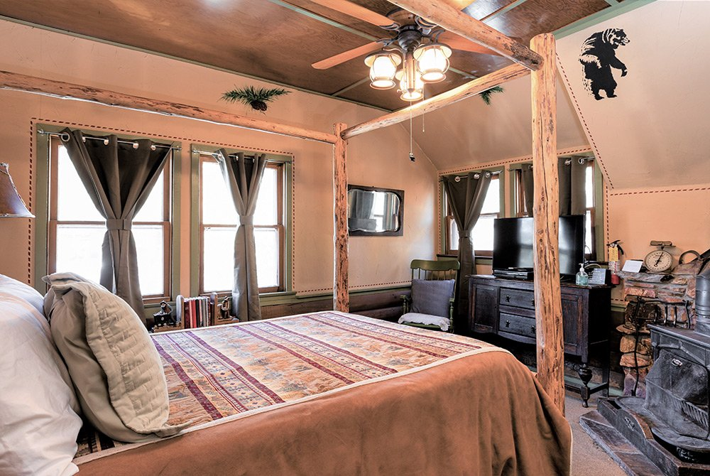 Framed bed in room with windows, fireplace, dresser, and television