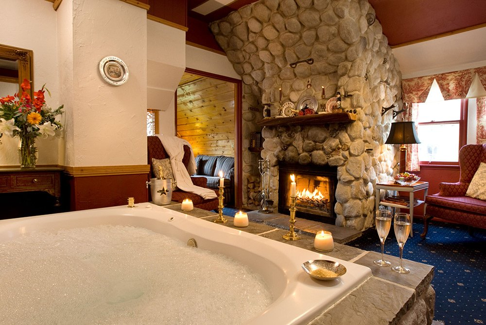 Large bathtub in bathroom with stone fireplace and comfy seating