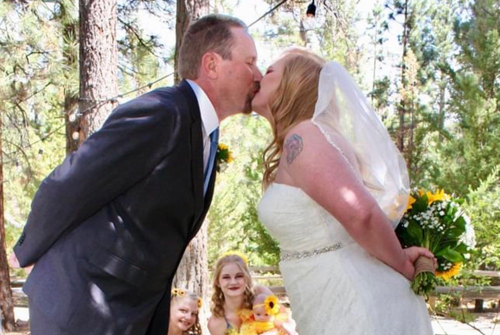Bride and groom kissing with their hands behind their backs