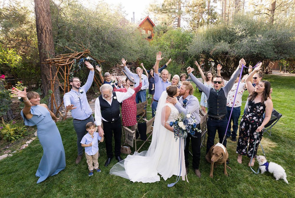 Wedding guests celebrating around bride and groom kissing