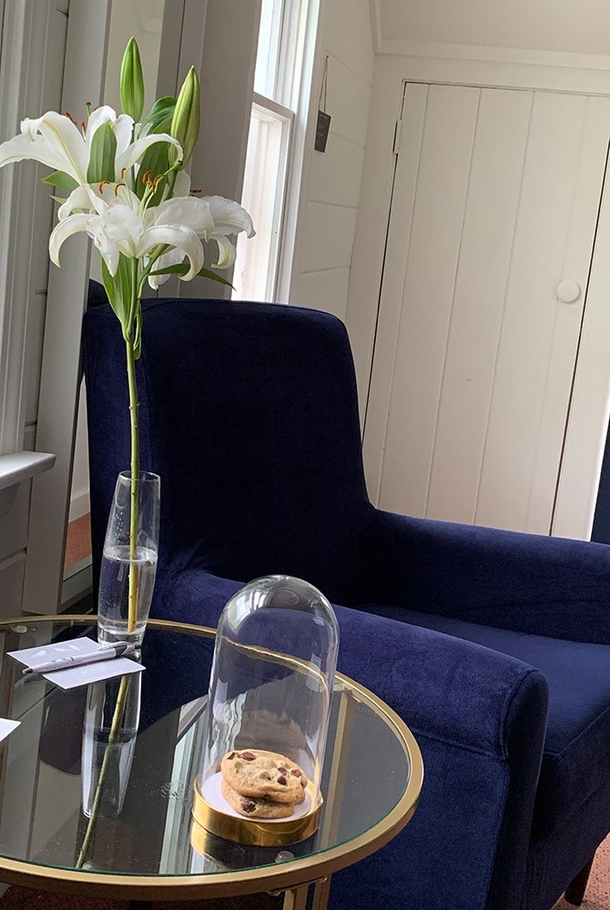 flowers and cookies on table next to chair