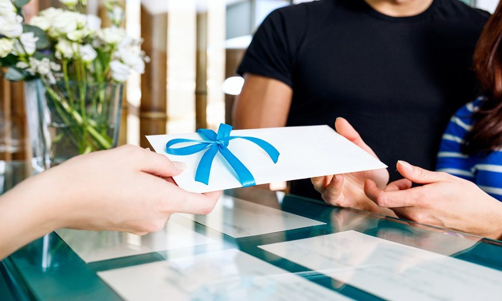 person handing couple gift envelope